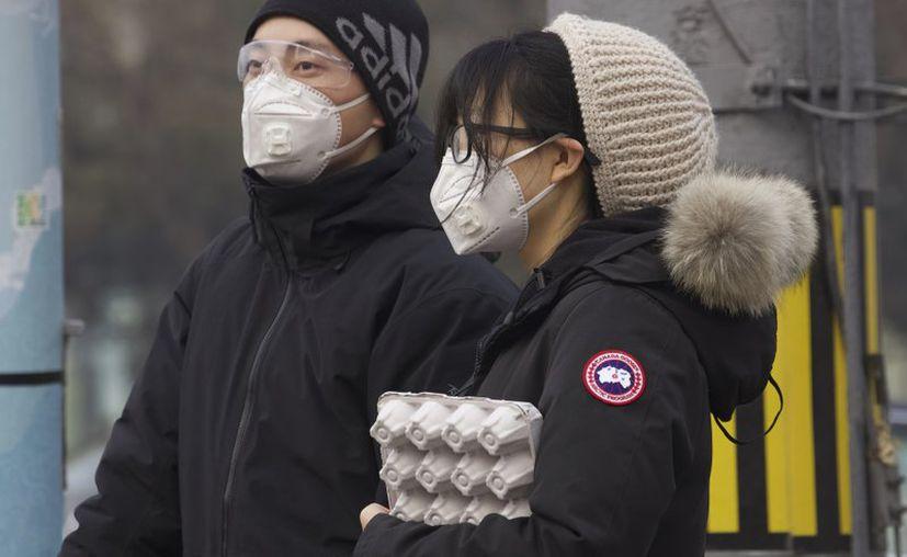 Residentes de Beijing, China se protegen con una mascarilla facial mientras esperan en un semáforo. (Foto/AP).