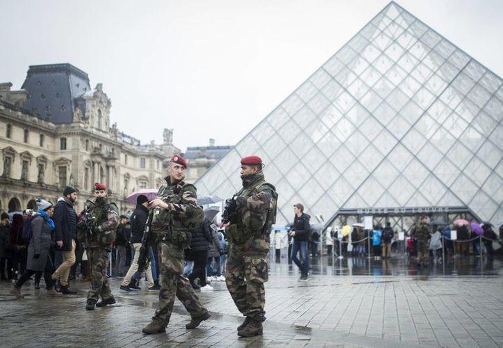 Patrullas de militares y agentes del Cuerpo Republicano de Seguridad, con armas de gran calibre, patrullan los alrededores del Museo del Louvre. (AP/Kamil Zihnioglu)
