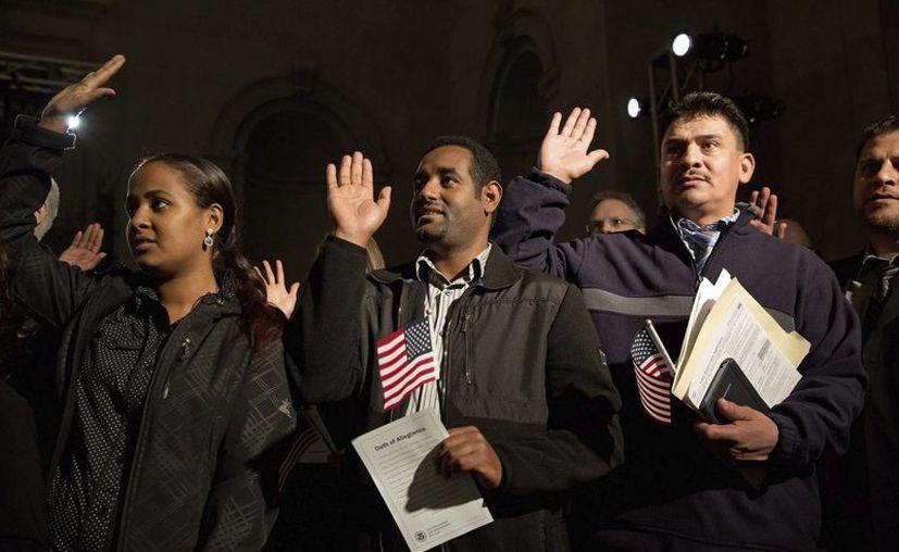 Varios inmigrantes realizan el juramento de lealtad tras recibir la ciudadanía estadounidense durante una ceremonia celebrada en el Archivo Nacional estadounidense en Washington, Estados Unidos. (EFE/Archivo)