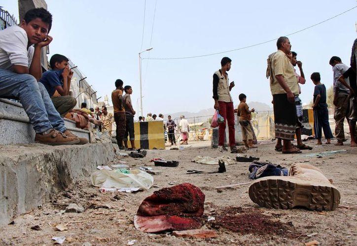 Varias personas se reúnen en un lugar donde hubo atentados terroristas en Aden, en el sur de Yemen, que dejaron decenas de víctimas. (Agencias)