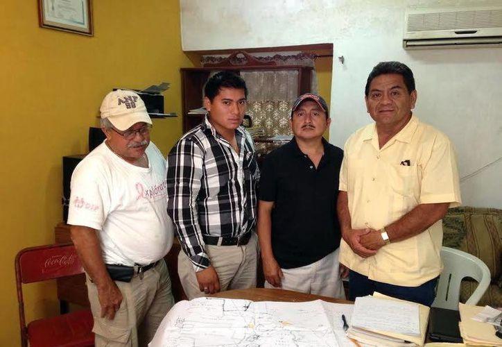 Miguel Ceballos Martín (derecha) y Gilberto Can Canul (de cuadros) con dos propietarios de un terreno, en el marco de una disputa en Hunucmá. (Israel Cárdenas/SIPSE)