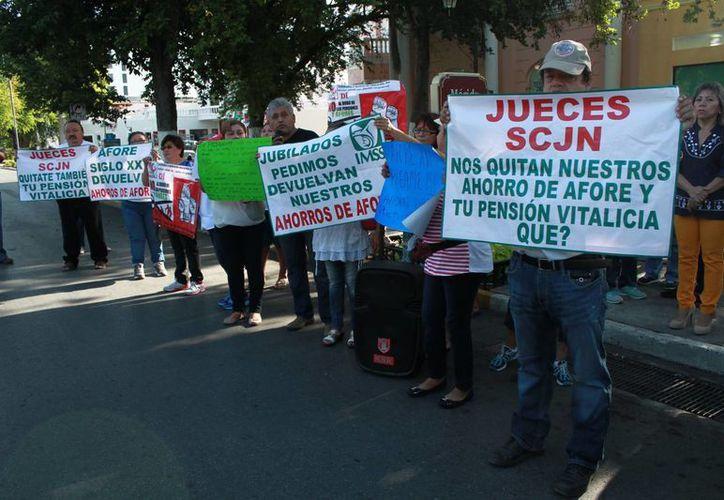 Alrededor de 20 exempleados del IMSS protestaron este lunes  frente a las oficinas de la Afore XXI ubicada en Paseo Montejo por 35.  (Foto: Jorge Acosta/Milenio Novedades)