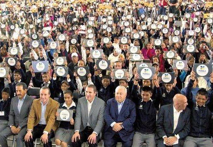 Rafael Moreno Valle y Emilio Chuayffet (centro) encabezaron la entrega de apoyos a estudiantes en Puebla, en el marco de las críticas hacia los paros de la CNTE en todo el país. (Milenio)