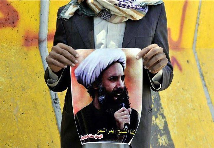 Una persona protesta con la imagen del clérigo chiita Nimr Baqir al-Nimr, considerado uno de los líderes de la Primavera Árabe que fue ejecutado este sábado junto a otras 46 personas. (EFE)