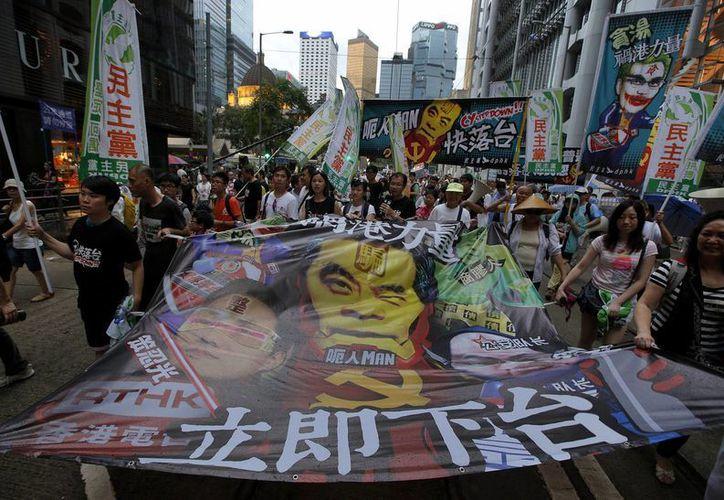 """Manifestantes llevan una lona en la que aparece el retrato del presidente del consejo ejecutivo de Hong Kong y las palabras """"renuncia ahora"""". (Agencias)"""