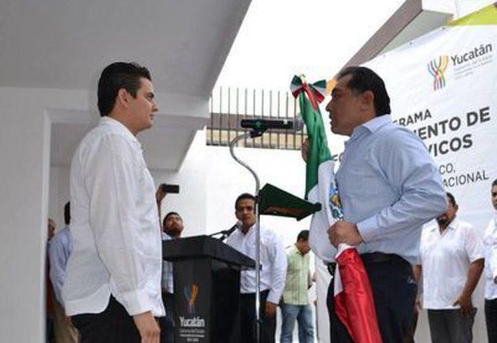 El secretario general de Gobierno, Víctor Caballero Durán, entre la bandera nacional al delegado del Conafe, Carlos Carrillo Paredes. (SIPSE)