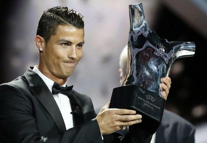 El delantero portugués del Real Madrid, Cristiano Ronaldo, que por estar lesionado no fue convocado para jugar con Portugal en septiembre,  posa con su trofeo de mejor jugador europeo de la temporada 2013/2014 según la UEFA. (EFE)