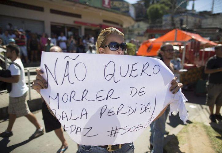 Una habitante de una favela carioca porta un cartel que reza 'no quiero morir por una bala perdida'. (AP)