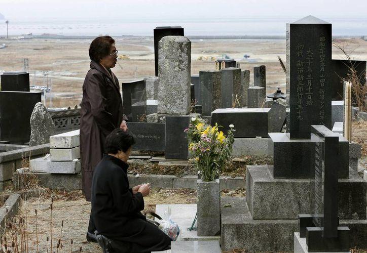 Dos mujeres oran durante un momento de silencio a sus muertos en la tragedia japonesa. (Agencias)