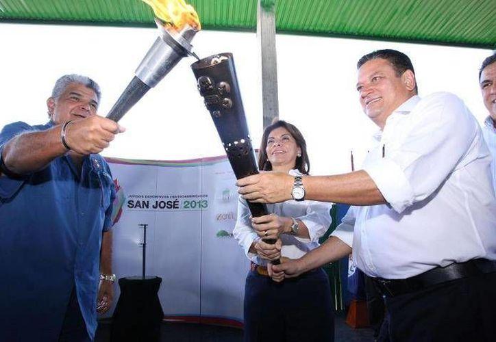 La presidenta Laura Chinchilla recibe la antorcha de los Juegos Centroamericanos San José 2013, en Paso Canoas. (Facebook oficial)