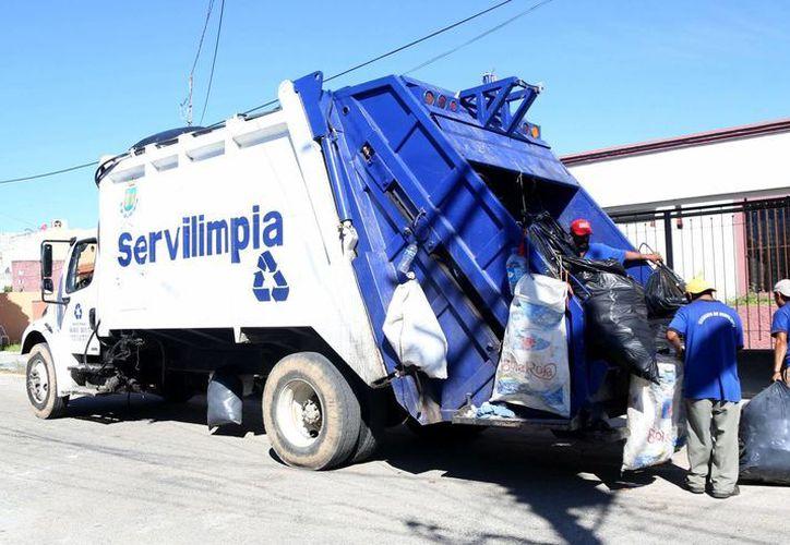 Desde ayer las empresas recolectoras atienden sus nuevas rutas. Imagen de un camión de Servilimpia en el acopio de desperdicios en una colonia de Mérida. (Milenio Novedades)