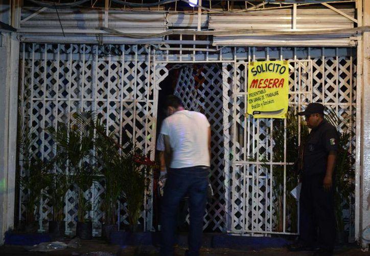 Peritos forenses trasladan un cuerpo durante la madrugada del miércoles en un bar de la ciudad de Acapulco, donde unos hombres irrumpieron en el lugar y asesinaron a tiros a dos trabajadoras y al encargado. (EFE)
