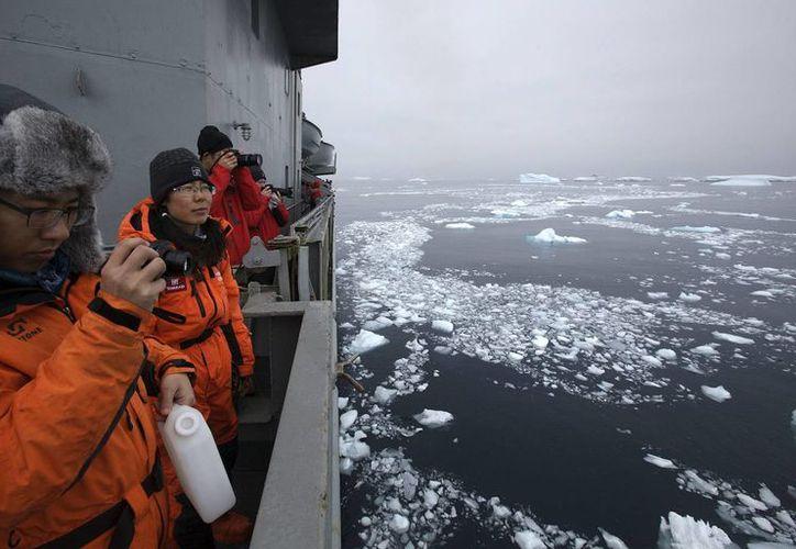 Dos científicos chinos toman fotos a bordo del buque de la Armada chilena Aquiles, durante su travesía por las Islas Shetland del Sur, Antártida. (EFE)