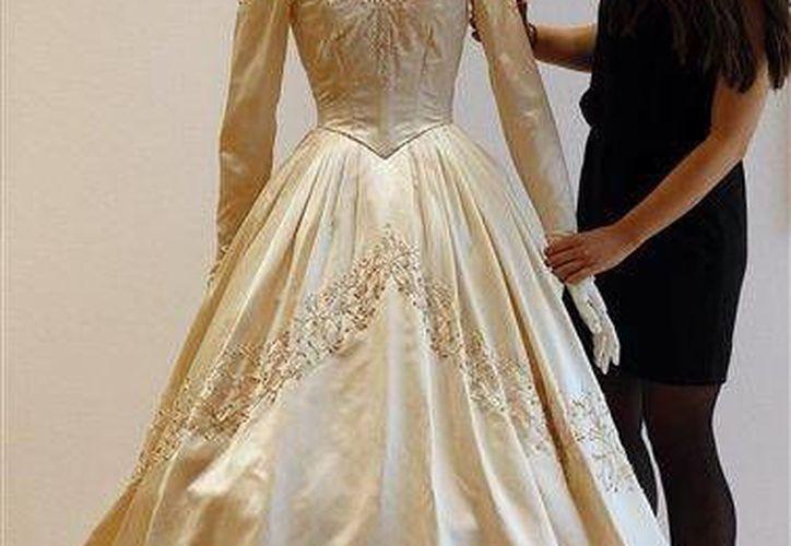 Una empleada de la casa de subastas Christie's ajusta el primer vestido de novia de Elizabeth Taylor (AP)