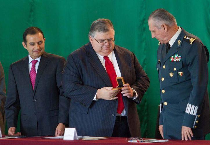 Cienfuegos Zepeda (d) al momento de recibir de Carstens la moneda conmemorativa. (Notimex)
