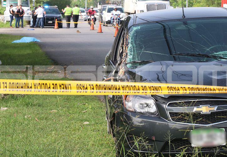 En primer plano, el auto que atropelló al peatón, cuyo cuerpo aparece al fondo. (Jorge Pallota/SIPSE)