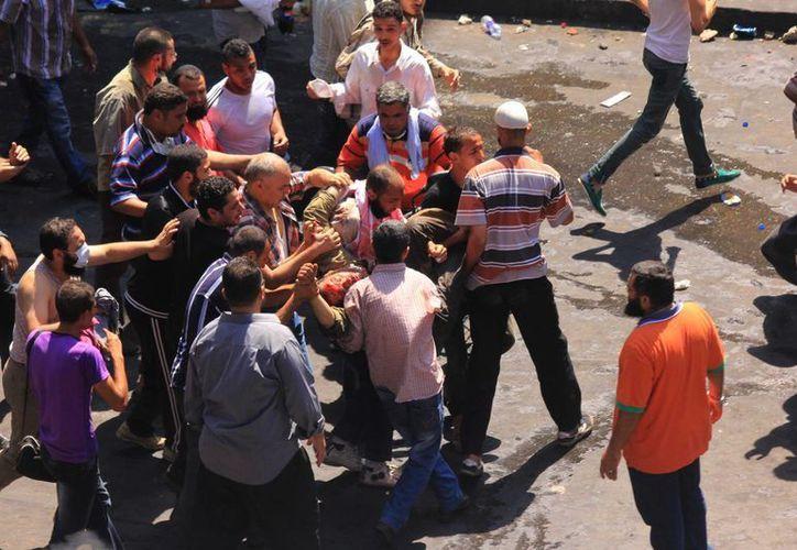 Seguidores del depuesto presidente Mohamed Morsi cargan a un hombre herido durante enfrentamientos con la Policía en Nasr City, distrito de El Cairo. (AP)