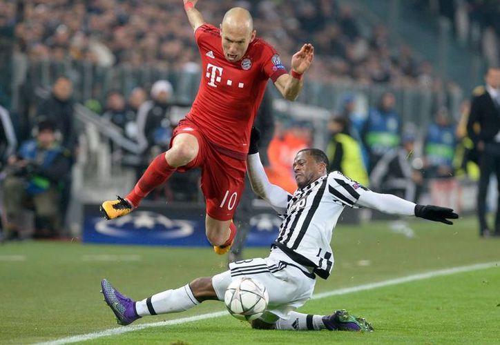 Arjen Robben (10), del Bayern Munich, esquiva la barrida de Patrice Evra, de la Juventus, en partido de octavos de final de la Champions League. (AP)