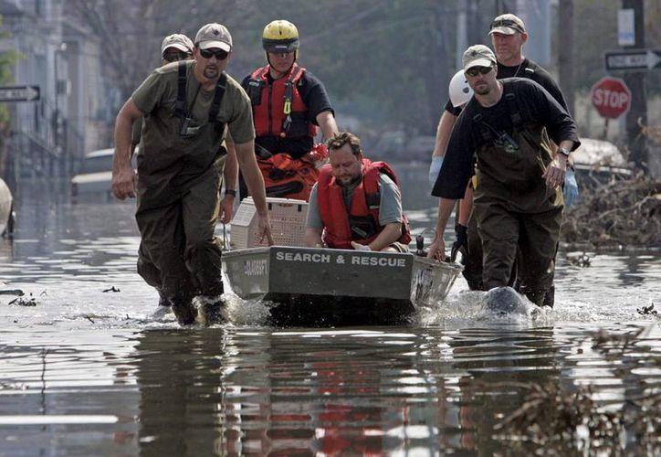Fotografía de archivo fechada el 13 de septiembre de 2005 que muestra a varios miembros de los servicios de rescate mientras ayudan a un hombre tras el paso del huracán Katrina en Nueva Orleans. (Archivo/EFE)