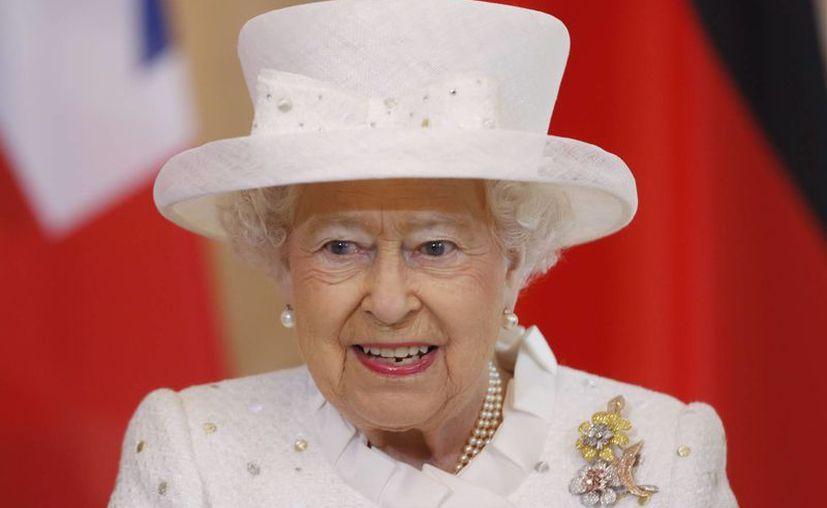 La reina Isabel II de Inglaterra tendrá que mudarse del palacio de Buckingham por reparaciones a la edificación. Imagen de hoy 24 de junio, en donde la soberana firma el libro de honores en Berlín, durante su visita oficial a Alemania. (Foto AP/Markus Schreiber, Pool)