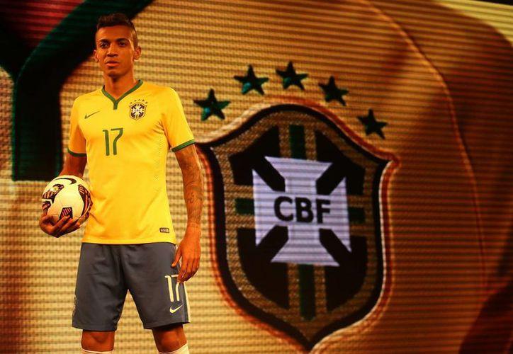 El futbolista brasileño Luiz Gustavo modela la camiseta con la que Brasil participará en el mundial 2014. La presentación se hizo en Río de Janeiro. (EFE)