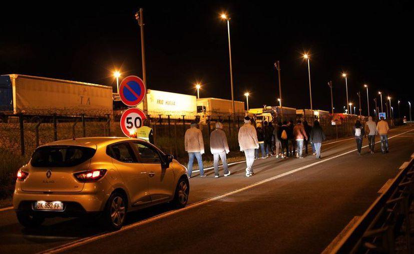 Un vehículo de seguridad del eurotúnel sigue a un grupo de migrantes que intentó cruzar la noche del miércoles 29 de julio de 2015 desde Calais, Francia, hacia Gran Bretala. (AP)