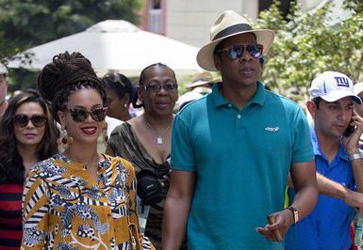 Beyonce y su esposo Jay Z (d) aparecen acompañados por guardaespaldas. (Agencias)