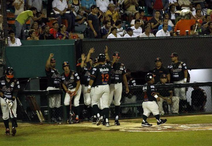 Los jugadores melenudos celebran su primera carrera, en el segundo acto. (Juan Albornoz/SIPSE)