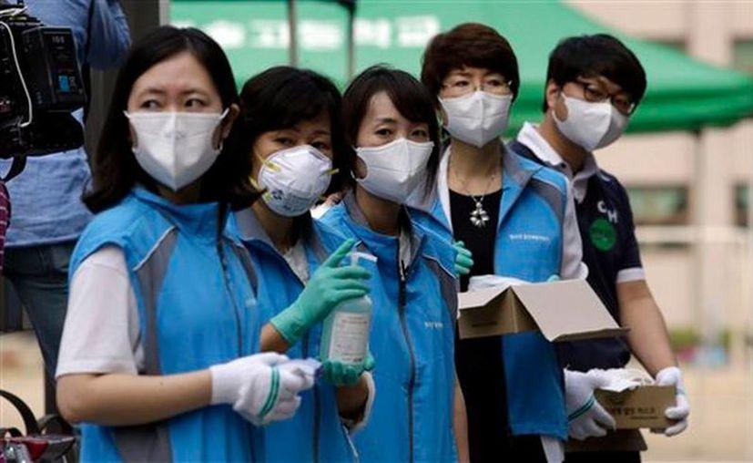 Las actividades cotidianas en el país asiático se han paralizado por la presencia de este virus peligroso. En la foto trabajadores surcoreanos de un centro comunitario equipados con máscara como precaución contra el MERS. (AP)