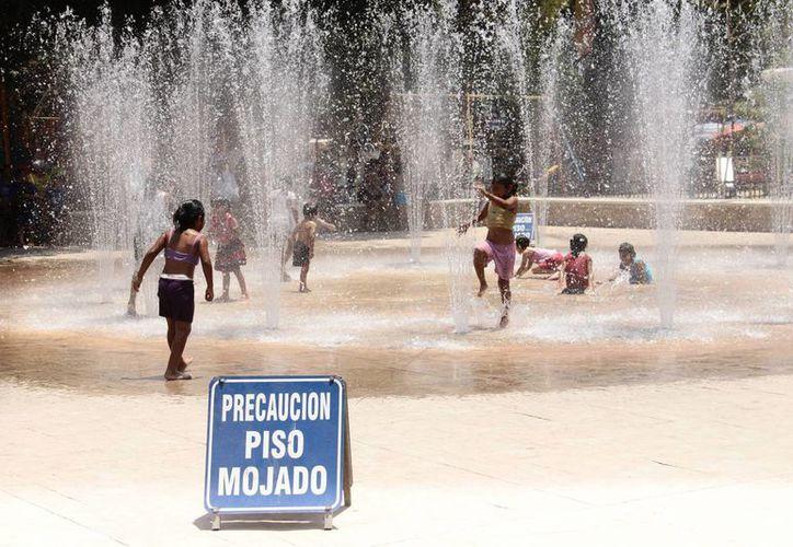 Las fuentes del Centenario fueron una buena opción para refrescarse este domingo, ante los más de 40 grados que se registran en Mérida. (SIPSE)