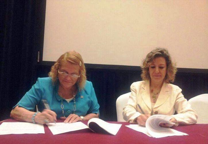 Las resctoras Elina Coral Castilla y Kitty Gaona Franco, durante la firma del convenio. (Cortesía/Uqroo)