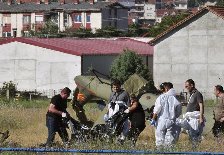 Agentes de seguridad e investigadores cargan el cuerpo de una víctima junto a los restos del helicóptero de la policía que se estrelló en Strumica, Macedonia. (EFE)