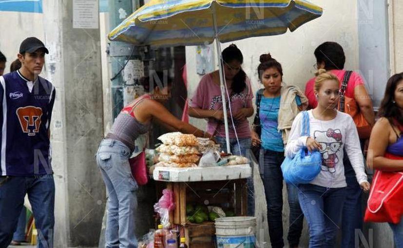 Miles de personas que no tienen un empleo fijo se ven en la necesidad de vender en las calles en esta contingencia su situación se ha agravado. (Novedades Yucatán)