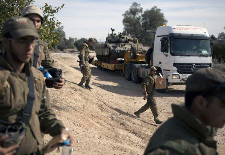 Soldados israelíes pasan junto a un camión que transporta un carro de combate, junto a la frontera con Gaza, en Israel. (EFE)