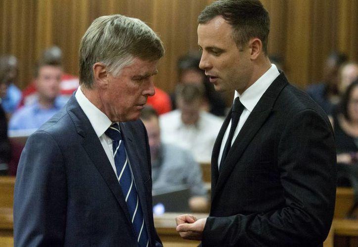 Oscar Pistorius, con uno de sus abogados, durante el juicio que se le sigue por haber matado a balazos a su novia el 14 de febrero del año pasado. (Foto: AP)