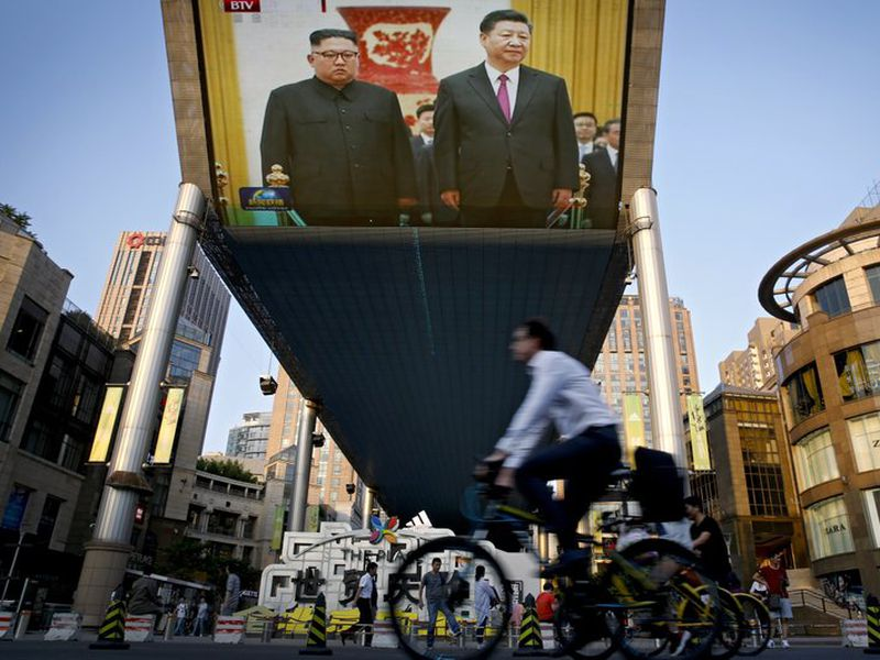 People bicycle past a giant TV screen broadcasting the meeting of North Korean leader Kim Jong Un and Chinese President Xi Jinping.