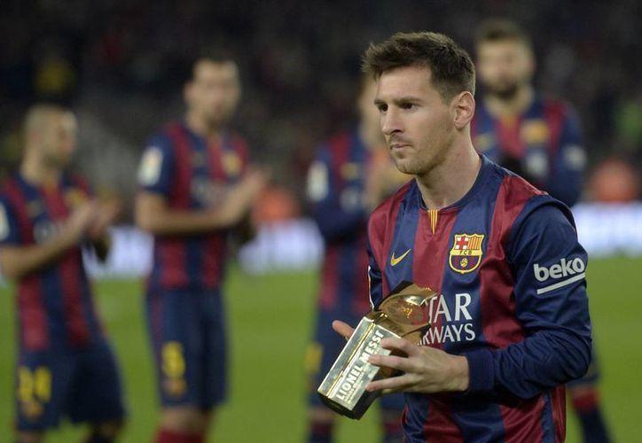 Lionel Messi con el reconocimiento que recibió por haber superado hace seis fechas el récord histórico de goles en la liga española. (AP)