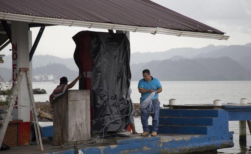 Trabajadores de una estación de gasolina en Guatemala la resguardan ante la llegada del huracán Earl, que tocará Belice este jueves. (AP)