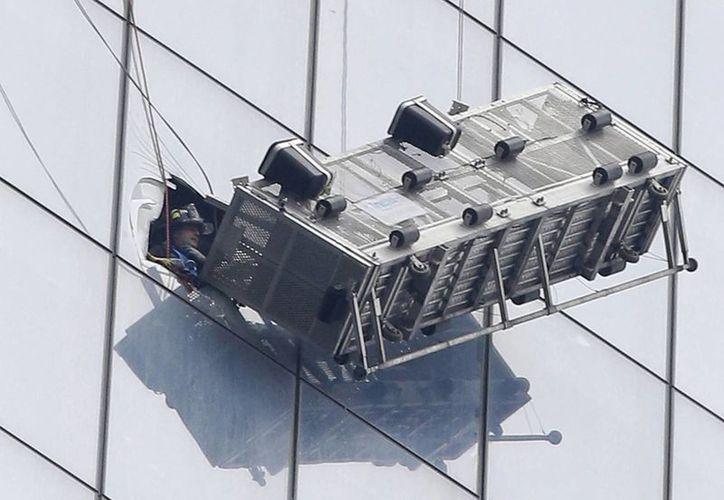 Un andamio cuelga de la fachada del World Trade Center en Nueva York, el miércoles, 12 de noviembre del 2014. Dos limpiaventanas tuvieron que ser rescatados por los bomberos. (Foto AP/Kathy Willens)