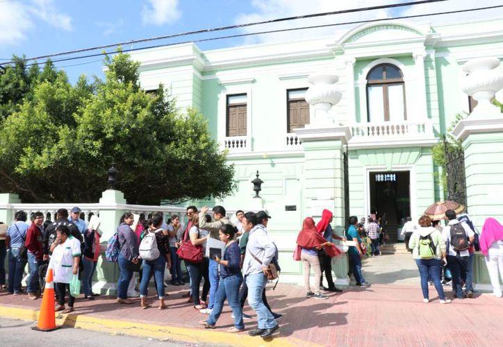 A las puertas de la Secretaría de Salud de Yucatán (SSY) se pudo observar un numeroso grupo de gente que esperaba ser atendida en busca de una plaza. (Fotos de Daniel Sandoval)
