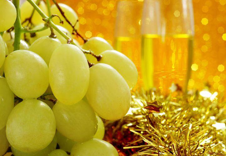 La tradición de consumir uvas por cada campanada en punto de las 12 de la noche. (Contexto)