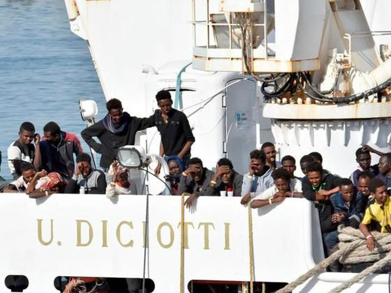 """Migrants wait to disembark from an Italian Coast Guard vessell """"Diciotti"""" as it docks at the Sicilian port of Catania, southern Italy."""