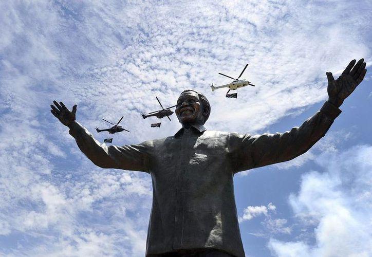 Helicópteros sobrevuelan una estatua de nueve metros del expresidente sudafricano Nelson Mandela afuera del complejo de Edificios de la Unión en Pretoria, Sudáfrica. (EFE)