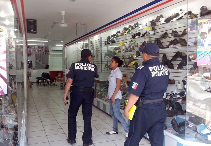 Agentes municipales revisan la zapatería donde ocurrió el robo al amparo de la noche. (Jorge Sosa/SIPSE)