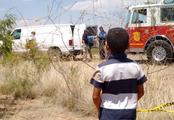 Un amiguito de Christopher mira cuando se llevan su cadáver en Aquiles de Serdán, Chihuahua. (tiempo.com.mx)
