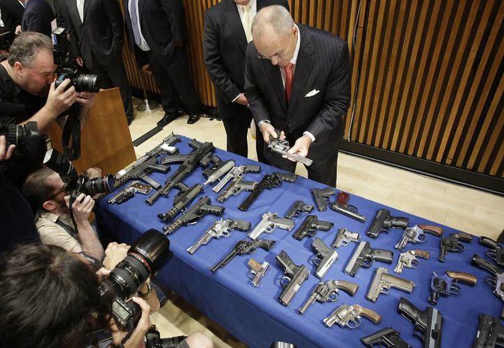 El comisionado de Policía Raymond Kelly analiza algunas de las armas incautadas. (Agencias)