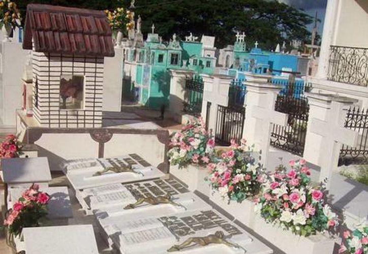 Esta es la foto captada en el interior del cementerio de Hoctún. En la parte de abajo, en primer plano, se observa una mano abierta con sus cinco dedos, que se plasma en la sombra de esa tumba. (Jorge Moreno/SIPSE)