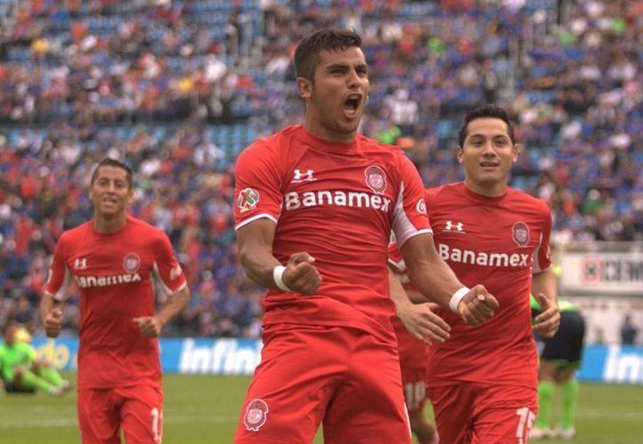 Miguel Ponce, del Toluca, celebra el primer gol en el partido frente La Máquina del Cruz Azul. Los Diablos Rojos se llevaron 3 puntos de la casa de los cementeros. (NTX)