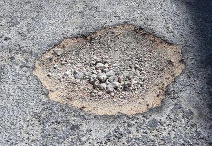 Las grietas que se hacen alrededor de un bache provocan el levantamiento de la calle. (Teresa Pérez/SIPSE)
