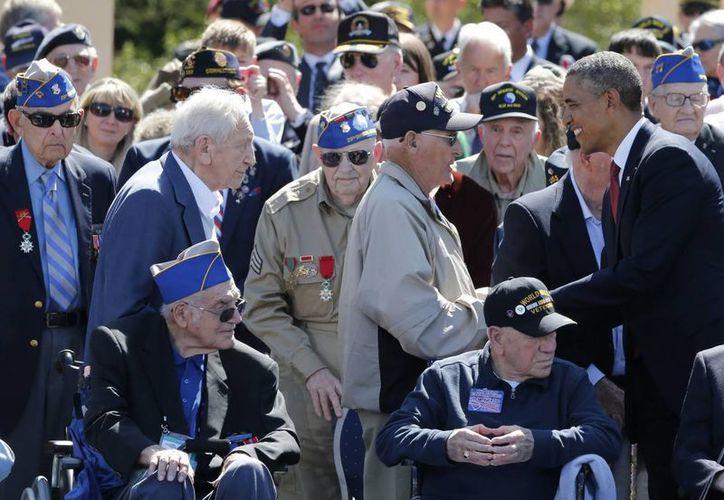 Obama (d) saluda a varios veteranos mientras participan en la ceremonia franco-estadounidense en el cementerio militar estadounidense y complejo conmemorativo de Normandía en Coeville-sur-Mer.  (EFE)